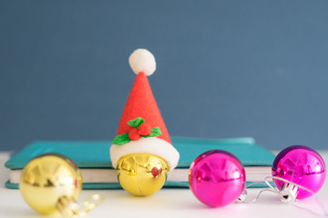 Christmas concept with copy space.Ornament balls, Santa Claus hat and note book with blue background.