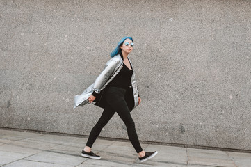 Girl wearing silver raincoat walking away