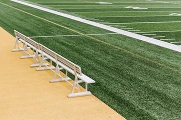Empty bench on sideline of field