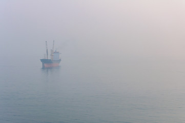 View of the cargo ship floating on the sea through the thick fog