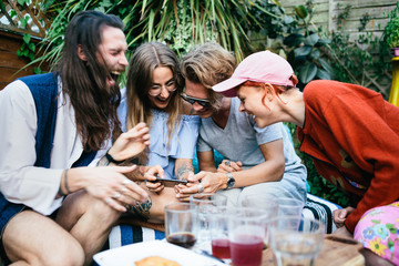 Four friends sitting outdoors looking at a phone screen and laughing hysterically