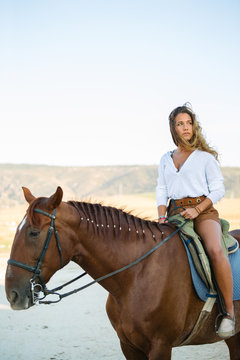 Young woman riding a white horse