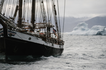 Old Vintage sailing vessel and Icebergs floating in the arctic close to greenland in the stormy weather.