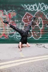 Clubkid guy doing street dance in front of a grafitti shutter