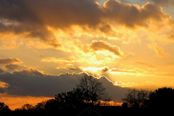 Sunset over the forest.Bright clouds,golden rays,dark clouds.