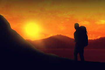 Silhouette of backpacker man hiking the mountain at sunset