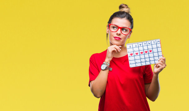 Young beautiful woman holding menstruation calendar over isolated background serious face thinking about question, very confused idea
