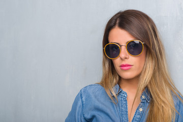 Young adult woman over grunge grey wall wearing retro sunglasses with serious expression on face. Simple and natural looking at the camera.