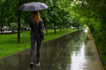 Woman walking with black umbrella under the rain