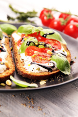 Bread with cream cheese and tomato for lunch table. Sharing antipasti on party or summer picnic time over wooden rustic background