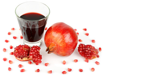 Pomegranate juice in a glass and ripe pomegranates. Isolated on white background. Free space for text. Wide photo.