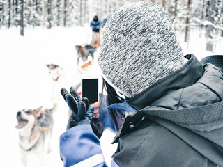 Woman taking photo of Husky dog sled in Finland Lapland