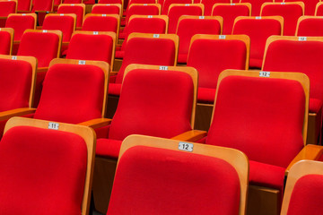 Red chairs in the auditorium of the theater or concert hall.