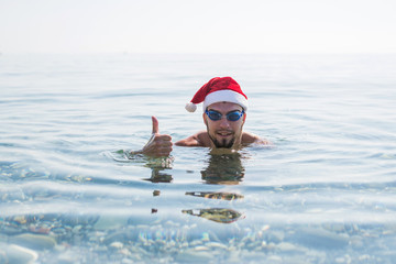 Man in a santa claus hat and swimming goggles thumbs up, christmas background.