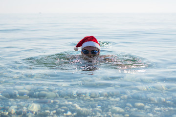 Man in a Santa Claus hat and glasses for swimming, christmas background.