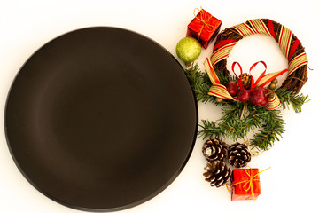 Black plates and vintage cutlery with Christmas decorations white backround
