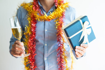 Close-up of man holding full flute and Christmas gift box. Unrecognizable man with tinsels around neck having fun at Christmas party. Event concept