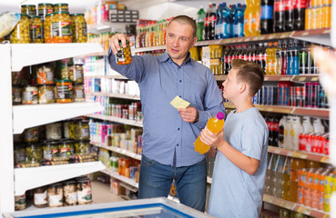 Young man and son choosing goods together with shopping list