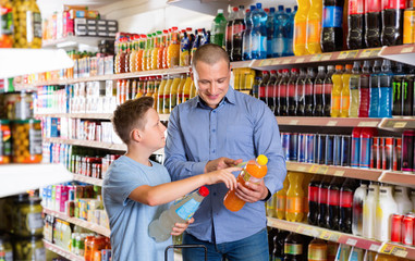 Smiling father friendly discussing with preteen boy while choosing beverages in food store