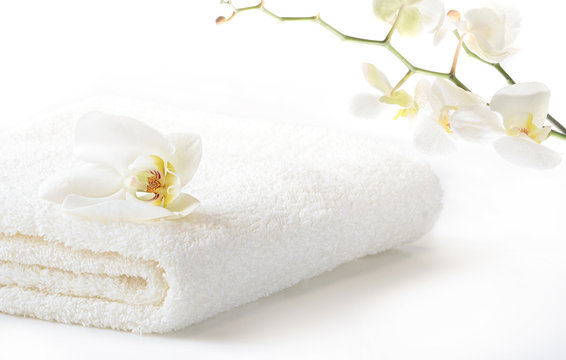 White Spa towel with Orchid flowers on branch on white background