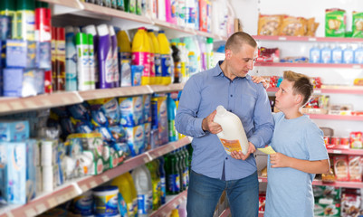 Portrait of father and preteen son buying household chemicals