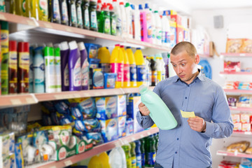 Male customer looking goods with shopping list in household shop