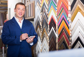cheerful man seller in picture framing studio with wooden details