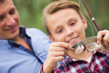 Smiling teenage boy catching on hook fish