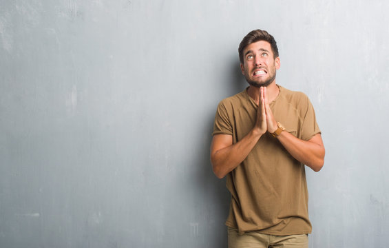 Handsome young man over grey grunge wall begging and praying with hands together with hope expression on face very emotional and worried. Asking for forgiveness. Religion concept.