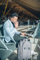 Young businessman is seated in the airport working with a laptop and carrying a suitcase waiting for his flight.