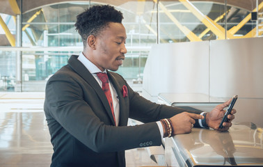 Young businessman looking for his mobile telephone on the check-in desk in the airport