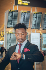 Young businessman looking at his smart watch in the airport in front of the departures information displays