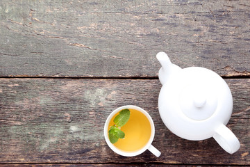 Cup of tea with mint leafs and teapot on wooden table