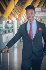 Young businessman with a suitcase stands up outside of the airport waiting for a car