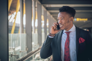 Young businessman going to the airport talking by telephone and smiling