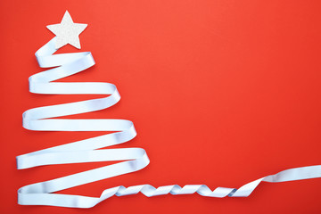 Blue ribbon in shape of christmas tree on red background