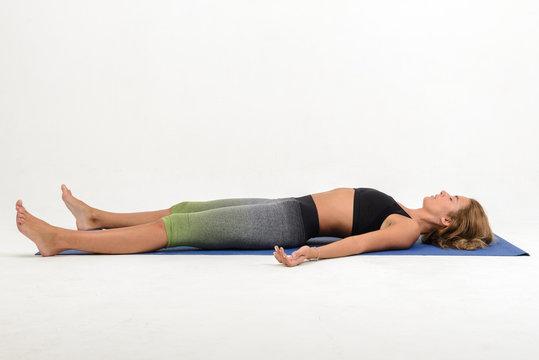 Beautiful young woman doing yoga on white background - shavasana