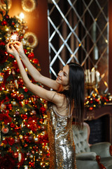 The concept of the Christmas party. A young brunette woman in a gold dress in sequins smiles and poses with sparklers on the background of  decorated room with a fireplace and a Christmas tree.