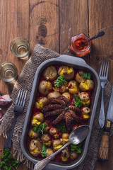 Baked octopus with potatoes, top view, copy space