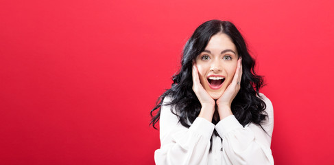 Surprised and excited young woman posing on a solid background