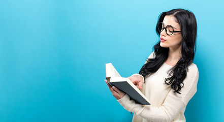 Young woman with a book on a solid background