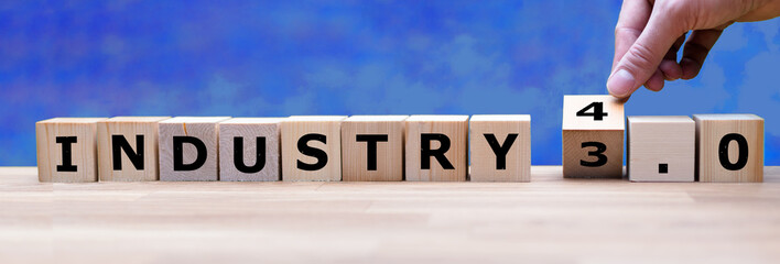 "Hand is turning a dice and changes the word ""Industry 3.0"" to ""Industry 4.0"""
