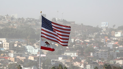 The United States and California State flags fly over Tijuana Mexico at the San Ysidro border crossing in San Diego