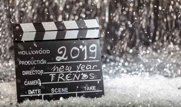 New year 2019 trends on movie clapper, abstract bokeh lights background