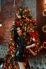 The concept of the Christmas party. Young brunette woman in a short black dress in sequins smiling and holding a Sparkler on the background of  decorated room with a fireplace and a Christmas tree.
