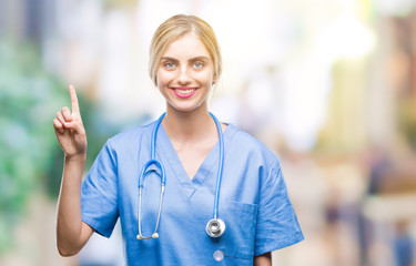 Young beautiful blonde doctor surgeon nurse woman over isolated background showing and pointing up with finger number one while smiling confident and happy.