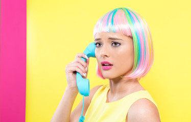 Young woman in a colorful wig talking on a retro phone on a split yellow and pink background