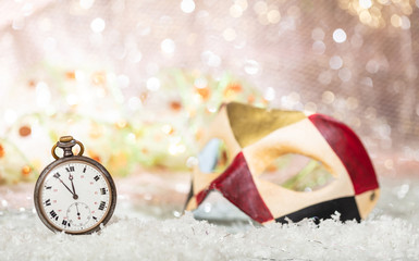 Carnival party. Minutes to midnight on an old watch, colorful mask, bokeh festive background
