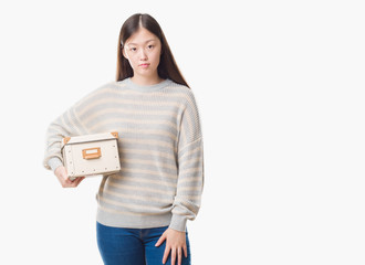 Young Chinese woman over isolated background holding a box with a confident expression on smart face thinking serious