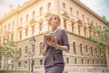 Elegant business woman uses a tablet in front of a office building